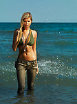 Beautiful young blond woman in army style outfit, jeans and bikini walking out of water