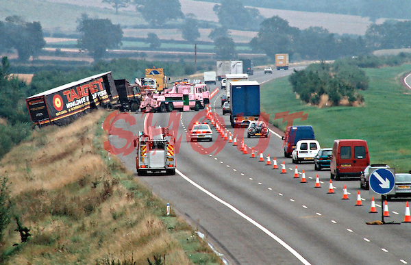 Fire, ambulance and breakdown services attend a road traffic accident. The H.G.V. lorry left the hard shoulder and went down the embankment. The tow truck is preparing to pull the lorry back up onto the motorway. Two lanes of the carrageway are closed causing tailbacks...© SHOUT. THIS PICTURE MUST ONLY BE USED TO ILLUSTRATE THE EMERGENCY SERVICES IN A POSITIVE MANNER. CONTACT JOHN CALLAN. Exact date unknown.john@shoutpictures.com.www.shoutpictures.com...Fire, ambulance and paramedic crews attend a road traffic accident. The lorry left the hard shoulder and went down the embankment. The tow truck is preparing to pull the lorry back up onto the motorway. Two lanes of the carrageway is closed causing tailbacks...© SHOUT. THIS PICTURE MUST ONLY BE USED TO ILLUSTRATE THE EMERGENCY SERVICES IN A POSITIVE MANNER. CONTACT JOHN CALLAN. Exact date unknown.john@shoutpictures.com.www.shoutpictures.com.