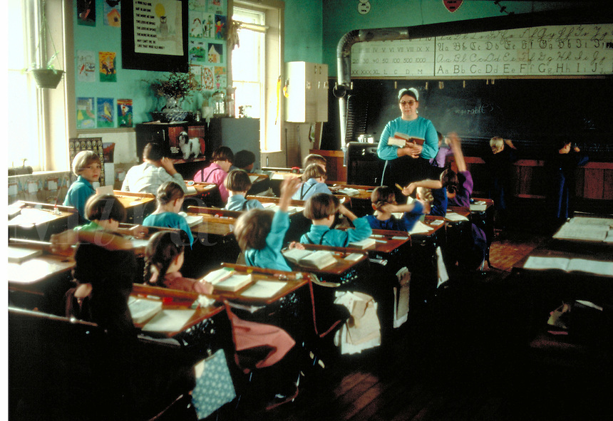 Amish teacher leads Amish children ages 6 to 12 in a class session at one room school. Amish schoolchildren and teacher. Lancaster Pennsylvania United States.