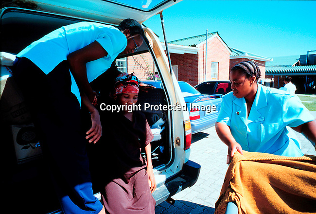 disiaids00351  Social Issues, Aids: Health. Busisiwe Mfeka, age 28, is dying of Aids, and coming home to her village in Izingolweni with her mother. She being transported by South Coast Hospice personel. Nov-99. Stretcher..©Per-Anders Pettersson/iAfrika Photos
