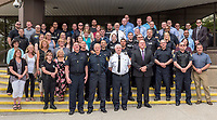 A large group of Sarnia Police Services officers and civilian workers pose on the front steps for aerial drone photographs.