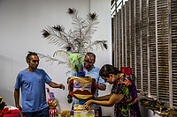 "RIO DE JANEIRO, BRAZIL - FEBRUARY 21, 2014: (Centre) Samy das Chagas, a visual artist and mental health patient, puts finishing touches onto a manequin made of empty boxes of prescription medecine that is used to treat schizophrenia and bipolar disorder, with the help of another patient and a (R)Polyanna Ferrari, a co-ordinator, in preparation for the annual Tá Pirando, Pirado, Pirou! carnival street parade at the Instituto Philippe Pinel psychiatric hospital on February 21, 2014 in Rio De Janeiro, Brazil. It looks like any of the other 450 or so street parties, locally called ""carnival blocks,"" that parade through Rio de Janeiro during the raucous pre-Lenten festivities that draw hundreds of thousands to the city each year. What makes this party different are its performers and organizers: psychiatric patients and their doctors, therapists, family members, neighbors and passers-by. The group, called Tá Pirando, Pirado, Pirou!, which roughly translates as ""We're freaking out, we already freaked out!"", began ten years ago when Brazil was in the process of dismantling its century-old system of mental asylums. A law passed in 2001 called for long-term outpatient psychiatric care to be offered primarily in community clinics. The number of such clinics increased more than fivefold in the following decade, while the number of asylum beds for psychiatric patients dropped 40 percent nationwide.<br /> <br /> Daniel Berehulak for The New York Times"