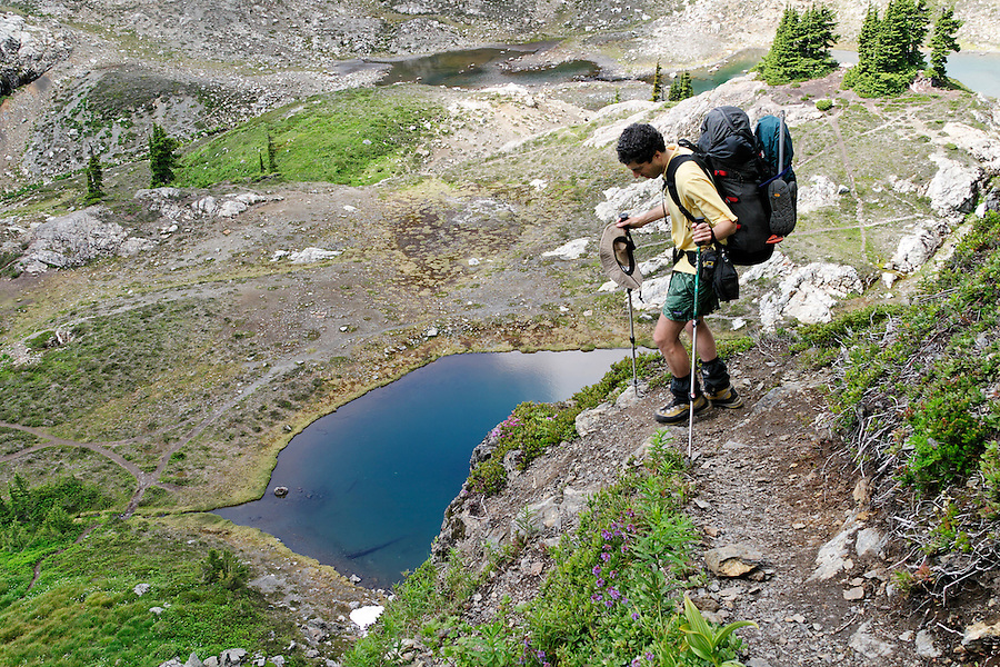 Man hiking down steep trail to alpine lakes in valley below Yellow Aster Butte, North Cascades, Whatcom County, Washington, USA