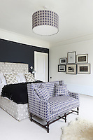 Matching fabric has been used to upholster a sofa and cover a lamshade in this bedroom