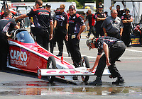 Aug. 2, 2014; Kent, WA, USA; Crew chief Richard Hogan wipes water off the front wing on the car of NHRA top fuel dragster driver Steve Torrence during qualifying for the Northwest Nationals at Pacific Raceways. Mandatory Credit: Mark J. Rebilas-