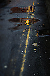 street lights reflected in a puddle on a dark cambridge street