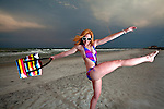 Young Pretty Red Haired Woman playing on a sea-side Beach