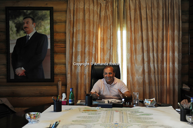 Ibrahim Ibrahimov, an Azerbaijani oligarch and billionaire, is seen during a meeting at the on-site office of the Khazar Islands project underneath a portrait of Azerbaijani President Ilham Aliyev near Sahil, Azerbaijan on July 18, 2012.  The brainchild of Ibrahimov, the artificial Khazar Islands project just southwest of the Azerbaijani capital Baku is being built at a projected cost of $100 billion with an anticipated 800,000 housing units.