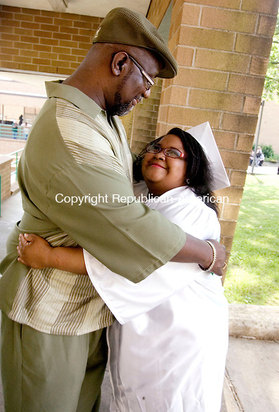 WATERBURY CT. 17 June 2014-061714SV08-Mailysa Hughes, 21, gets a hug from her godfather Michael Smith of New Haven during the graduation ceremony at Wilby High School in Waterbury Tuesday. <br /> Steven Valenti Republican-American