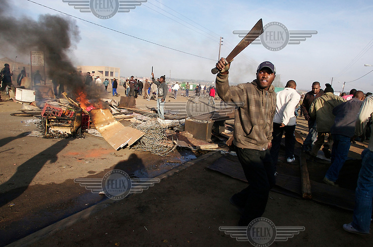Mobs with machetes set fire to belongings seized from foreign households in Ramaphosa informal settlement, East Rand, Johannesburg. Thousands of migrants have been forced to flee due to brutal xenophobic attacks on foreign African migrants living in South Africa's impoverished townships.