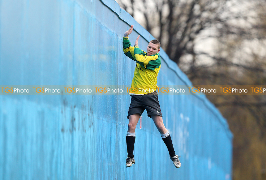 An Athletico Angels player seeks to retrieve a football from behind a high wall - Athletico Angels (yellow) vs Midfield - Hackney & Leyton Sunday League Football at East Marsh, Hackney - 21/02/10 - MANDATORY CREDIT: Gavin Ellis/TGSPHOTO - Self billing applies where appropriate - Tel: 0845 094 6026