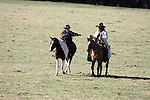 A cowboy and his son out on the range to round up cattle and the son is reaching for something from his Dad