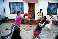 SOWETO, SOUTH AFRICA MAY 3: Children practice boxing outside a house on May 3, 2005 in the Orlando West section of Soweto, Johannesburg, South Africa. Soweto is South Africa&rsquo;s largest township and it was founded about one hundred years to make housing available for black people south west of downtown Johannesburg. The estimated population is between 2-3 million. Many key events during the Apartheid struggle unfolded here, and the most known is the student uprisings in June 1976, where thousands of students took to the streets to protest after being forced to study the Afrikaans language at school. Soweto today is a mix of old housing and newly constructed townhouses. A new hungry black middle-class is growing steadily. Many residents work in Johannesburg, but the last years many shopping malls have been built, and people are starting to spend their money in Soweto. <br /> (Photo by Per-Anders Pettersson)