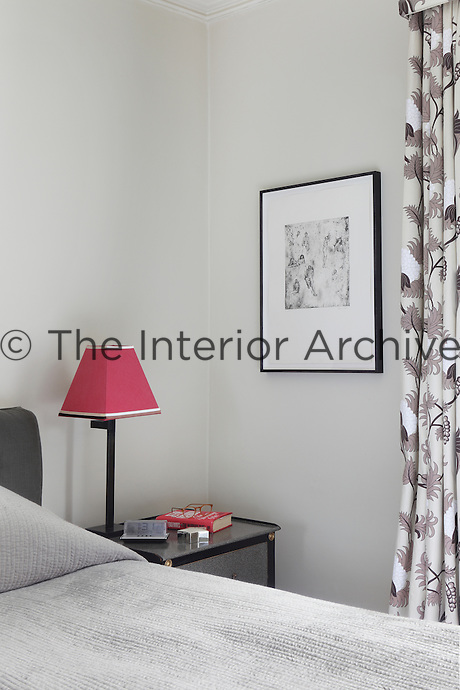 An etching of tiny nudes hangs beside the bed in this bedroom