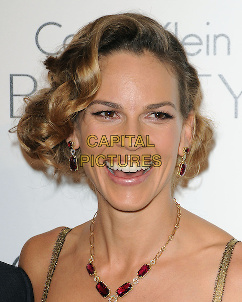 HILARY SWANK .walks the carpet as Elle Honors Hollywood's Most Esteemed Women in the 17th Annual Women in Hollywood Tribute held at The Four Seasons Beverly Hills in Beverly Hills, California, USA, October 18th 2010..portrait headshot smiling red earrings necklace stone gold .CAP/RKE/DVS.©DVS/RockinExposures/Capital Pictures.