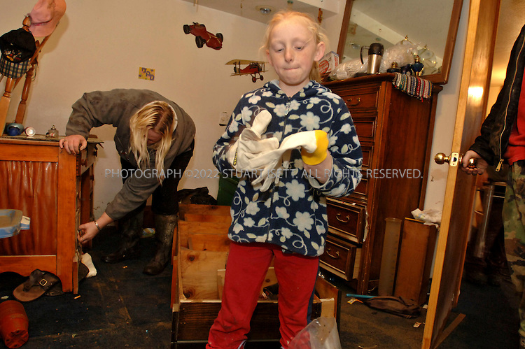 11/10/2006--Hamilton, WA, USA..8 year old Jamie Harris and her mother Stacey Harris (behind) clean up flood damaged belongings from their home in Hamilton, Wash., a flood-prone town on the Skagit River, after 4 feet of water covered the streets and town. With a population of about 330 people, some local residents want the town moved away from the river...Photograph By Stuart Isett.All photographs ©2006 Stuart Isett.All rights reserved.