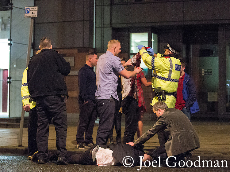 © Joel Goodman - 07973 332324 . 21/12/2013 . Manchester , UK . A man lies in the road and another has a bleeding arm following a fight on the city's Charlotte Street . Christmas revellers out in the rain in Manchester on Mad Friday , the last Friday night before Christmas which is typically one of the busiest nights of the year for police and ambulance crews . Photo credit : Joel Goodman