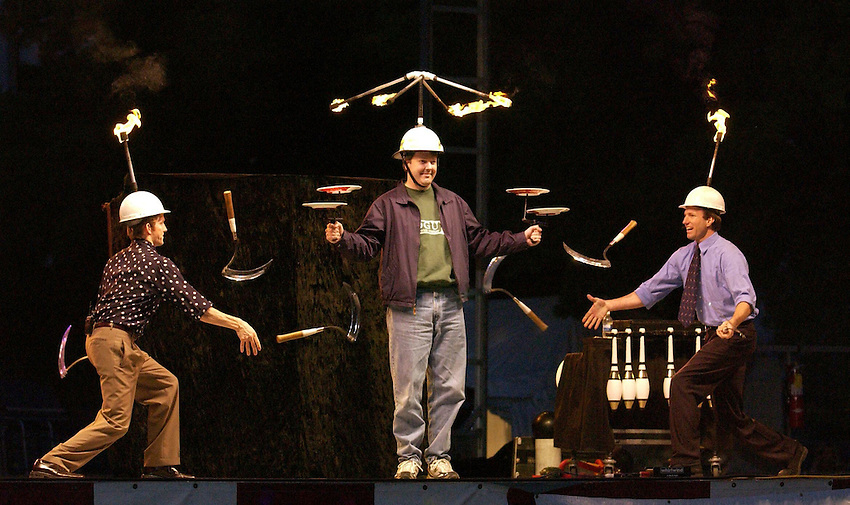 Jon Wee and Owen Morse juggle six sickles as a volunteer named Richard from the audience wears torches and holds spinning plates.  The act, The Passing Zone, amazed the crowd at the Publix stage at Panoply. Bob Gathany/Huntsville Times