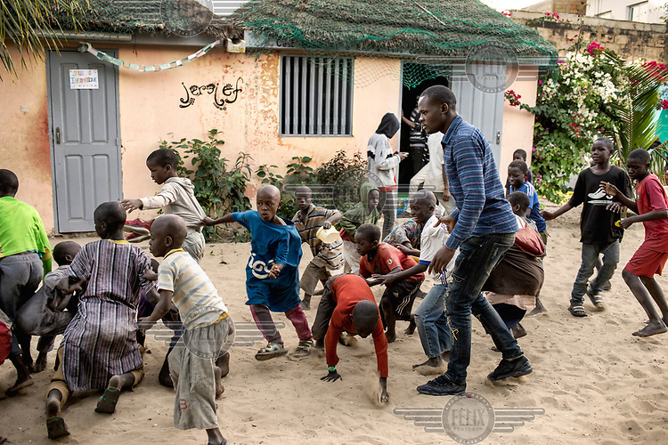 Children playing at the Maison de la Gare, a charity that seeks to rehabilitate ex-Talibe (children who live and study the Koran at a Daara, religious school). <br /> Talibe often have issues that stem from being separated from their parents at a young age and the abuse they endure at the Daaras where they are expected to beg to raise money for the Daara's marabout and to get food to fed themselves.