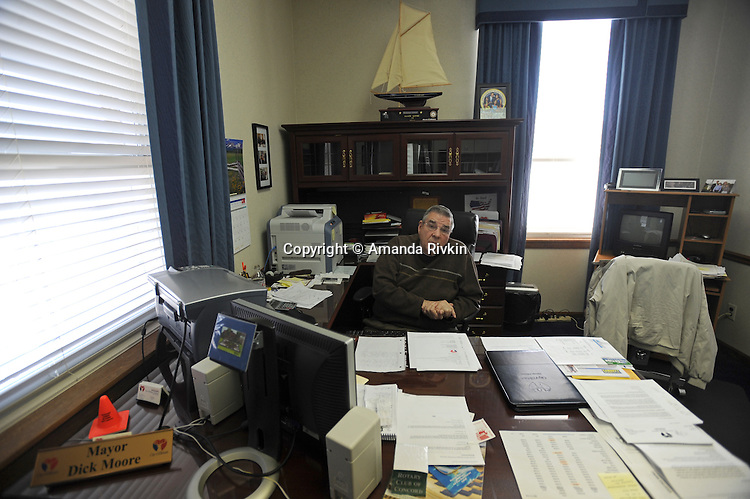"""Elkhart Mayor Dick Moore in his office in Elkhart, Indiana on April 8, 2009.  Elkhart has seen a surge in unemployment in the last year from 4.5% in 2008 to 20% this year and Obama has visited the town three times, including his first stop after arriving in Washington as the U.S. President to promote """"bail out"""" and stimulus spending during the current global recession; Moore has a photograph of Obama and his family in his office (right of sailboat), and says Obama's wishes to help his community are genuine, based upon their discussions """"me and him""""."""
