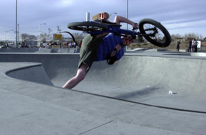 A BMX rider performs a footplant out of a bowl ramp at Los Altos Skatyepark in Albuquerque, NM in 2002.