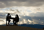 A couple of women in silhouette sit on a bench and talk against a background of building clouds at Zabriski Point, Death Valley National Park.