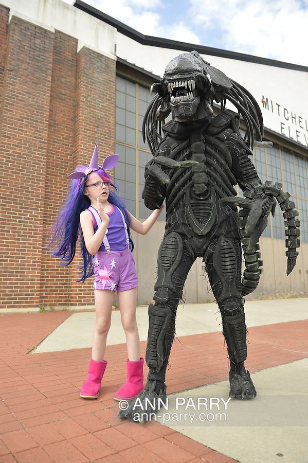 Garden City, New York, U.S. - June 14, 2014 - A young girl in a Twilight Sparkle costume from My Little Pony pretends to be scared of her father in an Alien costume, based on Alien VS Predator movie, in front of an historic Mitchel Field hangar at Eternal Con, the annual Pop Culture Expo, with costumes, Comic Books, Collectibles, Gaming, Sci-Fi, Cosplay, Horror, and held at the Cradle of Aviation Museum on Long Island.