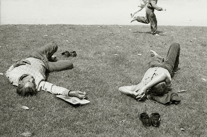 Children run past two men sleeping on the grass in a public park in Barcelona.<br />