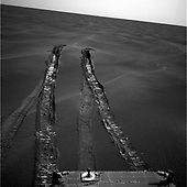 """Pasadena, CA - June 20, 2005 -- The wheels of NASA's Mars Exploration Rover Opportunity dug more than 10 centimeters (4 inches) deep into the soft, sandy material of a wind-shaped ripple in Mars' Meridiani Planum region during the rover's 446th martian day, or sol (April 26, 2005). Getting the rover out of the ripple, dubbed """"Purgatory Dune,"""" required more than five weeks of planning, testing, and carefully monitored driving. Opportunity used its navigation camera to capture this look back at the ripple during sol 491 (June 11, 2005), a week after the rover drove safely onto firmer ground. The ripple that became a sand trap is about one-third meter (one foot) tall and 2.5 meters (8 feet) wide.<br /> Credit: NASA-JPL via CNP"""