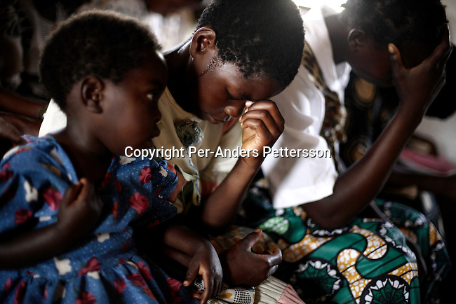 GALUFU, MALAWI NOVEMBER 12: Unidentified children pray during a Sunday service at a church on November 12, 2005 in Galufu, Malawi. Many people come to the church to pray for rain and a successful harvest. Most people in the village are poor and hungry, and cannot afford to buy maize at the market. The price is twice as much as the government subsidized prices. The government used to sell subsidized maize and fertilizer but not anymore. Many in the village eat mangoes and even boil unripe ones, as they cannot afford to buy anything else. The harvest was very bad in 2005 and the next one, due in April 2006 I uncertain because of lack of rains and drought. The village has seen an increase in poverty the last few years due to drought and HIV/Aids. Southern Africa has been hit by a severe hunger crisis due to drought and poverty. An ever-increasing HIV/Aids rate adds to the misery. Malawi is one of the worst hit areas and Galufu village is a typical small village that has become victim of this poverty spiral. (Photo by Per-Anders Pettersson)