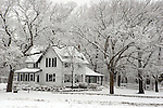 A house surrounded by fluffy snow covered trees at a rural farm in rural Wisconsin