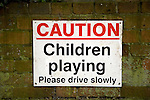 Caution Children playing please drive slowly sign on brick wall