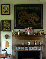 A painting of a tiger hangs above the fireplace with Delft tiles built into the fire surround