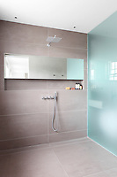 A spacious tiled wet room with an opaque glass screen and a cupboard set in a recess.