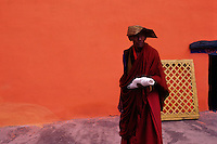 A monk in front of an orange wall, the Jokhang Temple, Lhasa.