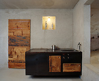 In the kitchen a small alcove displays an illuminated shrine above a cast iron kitchen island with an integral hob and sink whilst a rough-hewn pine door is juxtaposed with raw concrete walls