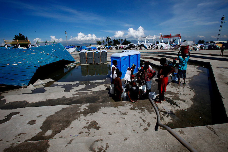 Nov 10, 2010 - Port-au-Prince, Haiti.Residents of a tent city in the Cite Soleil area of Port-au-Prince, Haiti gather water from pipes just yards from portable toilets and flood waters from Hurricane Tomas Wednesday, November 10, 2010 as fears of a Cholera outbreak spread through the area just two days after cases of the infection were confirmed in the area, the poorest slum in Haiti's capital. Officials from the Pan American Health Organization warn that Haiti's cholera epidemic, spread primarily through consuming infected water and food, is likely to grow much larger in the wake of Hurricane Tomas.  (Credit Image: Brian Blanco/ZUMA Press)