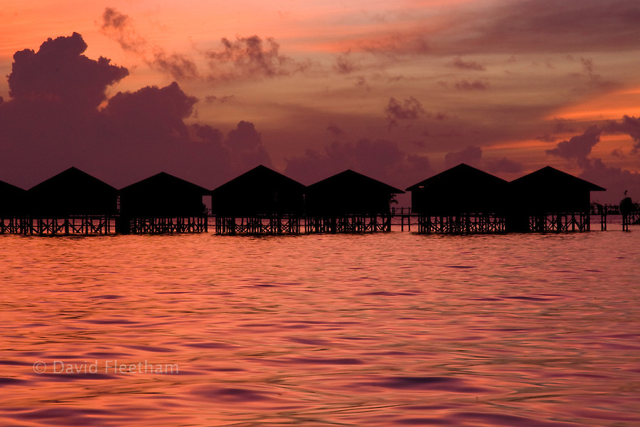 The sky lights up the accomodations over the ocean after sunet at the Sipidan Water Village off Mabul Island, Malaysia.