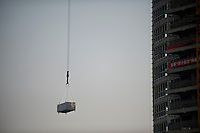 Daytime landscape view of construction materials hanging on a construction crane cable on the side of the Hongxin Office Building at the Yaohui International City construction site at the intersection of 103 Guo Dao and Xi Da Wang Lu in Cháoyáng Q? in Beijing.  © LAN