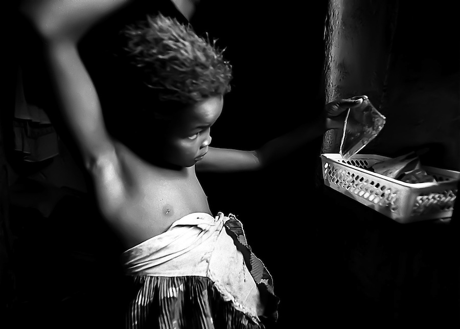 Brenda brushes her hair before church. The small piece of mirror in her hand is a much treasured item which the children take turns using when grooming themselves.