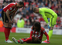 Jason Denayer of Sunderland (C) is injured on the ground being spoken to by team mates John O'Shea (L)  and Jordan Pickford of Sunderland (R) during the Premier League match between Sunderland and Swansea City at the Stadium of Light, Sunderland, England, UK. Saturday 13 May 2017