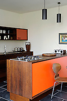 An open-plan kitchen in Scandinavian Modern style in a homely, contemporary space. The wooden kitchen units were handmade in water-resistant iroko with orange laminate on the door fronts and chamfered edges. The orange contrasts beautifully with the Brazilian black slate flooring.