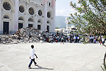A boy passes in front of the rubble of the destroyed national cathedral during a church service on July 11, 2010 in Port-au-Prince, Haiti.