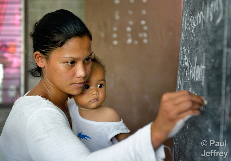 Holding her baby, a woman writes on the blackboard as she participates in an adult literacy class in the village of Magsaysay, in New Bataan in the Compostela Valley on Mindanao Island in the southern Philippines.