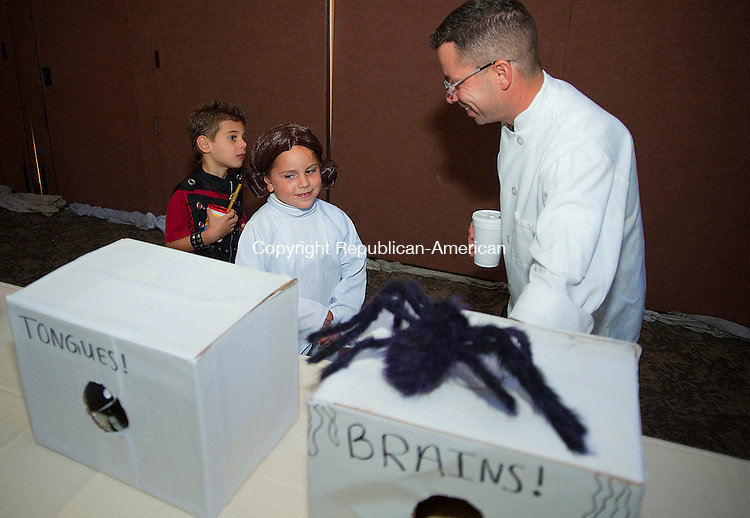 WATERTOWN- 102713JS02- Erik Parks, General Manager at Watertown Golf Club, right, tries to convince Sarah Krayeske, 6, of Watertown, center, and Spencer Dickson, 5, of Southing to touch &quot;tongues&quot; and &quot;brains&quot; in the haunted house during a halloween party Sunday at the Watertown Golf Club in Watertown. <br /> Jim Shannon Republican-American