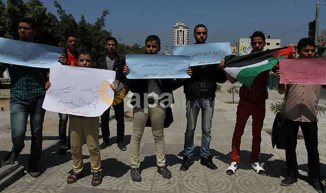 Palestinian youths hold banners during a protest to calling the national reconciliation, in Gaza city on April 22, 2014. A delegation representing the PLO is expected to arrive in Gaza on Tuesday evening for reconciliation meetings with Hamas, a Fatah spokesman said. Photo by Mohammed Asad