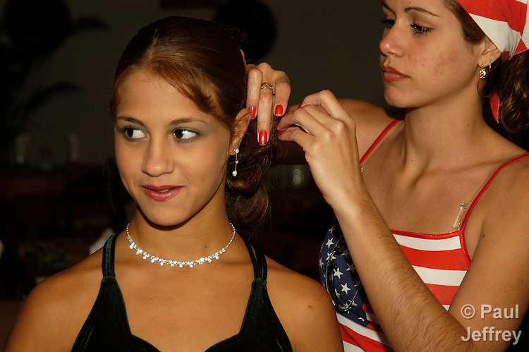 "A girl gets her hair arranged by a relative in preparation for her 15th birthday party. The party for such ""quincineras"" is a major social event in Cuban family life."