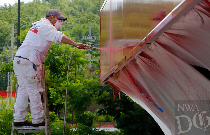 NWA Democrat-Gazette/DAVID GOTTSCHALK - 6/2/15 - Felix Roa, with Felix and Maria Clean and Paint of Fayetteville, applies a second coat of paint to the car port above the vacuum station at the Spot-Not Car Wash on Township Street in Fayetteville Monday June 1, 2015. Roa was using a special red metal paint that would bond to the surface.