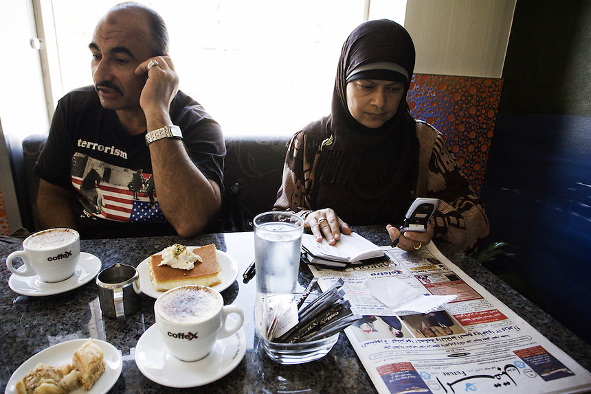 Mamdouh and Maha Habib make campaing calls on their mobile phones at an Arabic cafe in Granville, western Sydney, March 2007. Much of the Habib campaign's organisation was completed via cell phones by a team of four volunteers while on the road around Sydney.