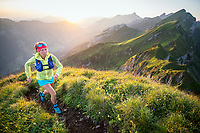 A woman trail running at sunrise on the Rophaien, Switzerland